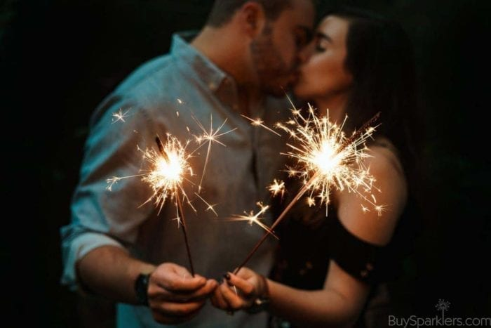 couple kissing holding sparklers